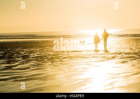 A couple walking on the beach in the evening - Stock Photo