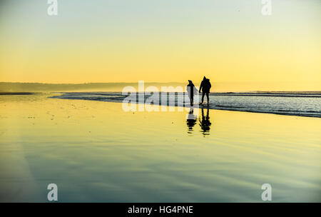 A young couple in love holding hands on a beach at sunset. - Stock Photo