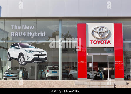 Toyota car centre facade wit new RAV4 Hybrid picture on display. Toyota RAV4 was the first company compact crossover - Stock Photo