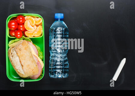 Sandwich, small tomatoes, tangerine in plastic lunch box and bottle of water on black chalkboard. - Stock Photo