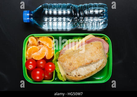 Sandwich, small tomatoes, tangerines in plastic lunch box and bottle of water on black chalkboard. - Stock Photo