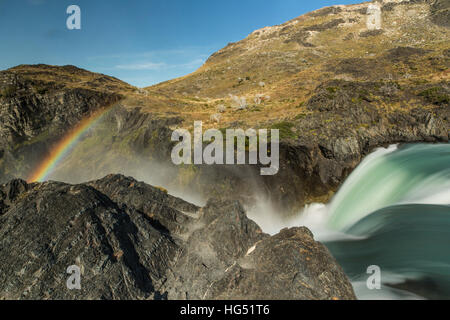 A rainbow in the mist of the Salto Grande Waterfall on the Rio Paine, or Paine River, in Torres del Paine National - Stock Photo