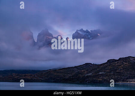 The Cuernos del Paine and Monte Almirante Nieto appear through a hole in the clouds.  Torres del Paine National - Stock Photo