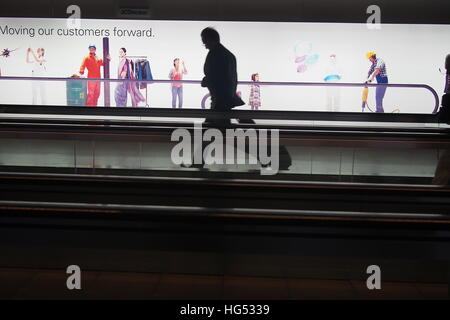 man rushing on moving walkway at an airport