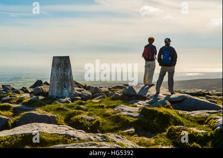 Walkers at west summit of Ward's Stone in the Forest of Bowland Lancashire England looking towards Morecambe Bay - Stock Photo