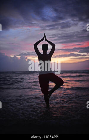 Young woman doing yoga tree pose at sunset,  Hikkaduwa beach, Sri Lanka - Stock Photo