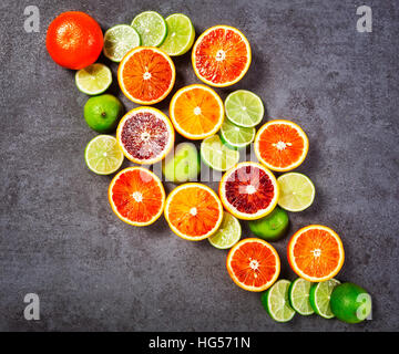 Citrus fruit background with slices of lime and blood orange as healthy eating and dieting concept, top view, flat - Stock Photo