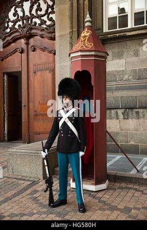 Denmark, Copenhagen, Christiansborg Palace, courtyard, soldier in guardsman's uniform guarding entrance - Stock Photo