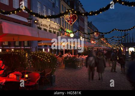 Denmark, Copenhagen, Nyhavn, Christmas market stalls and cafes lining cobbled quayside at night - Stock Photo