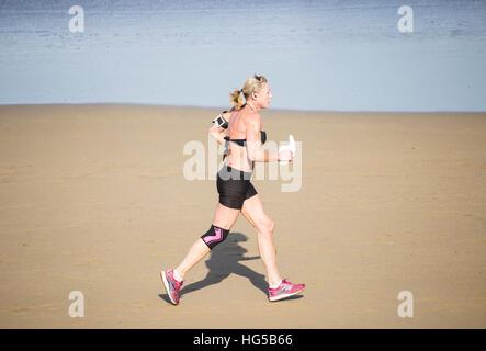 Mature woman running on beach. - Stock Photo