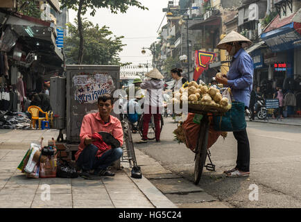 Urban street business scene in Hanoi. Man cleaning shoes and woman selling vegetables on bicycle. - Stock Photo