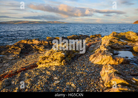 Rocky shore near Catacol looking out across the Kilbrannan Sound to Mull of Kintyre, Isle of Arran, North Ayrshire, - Stock Photo