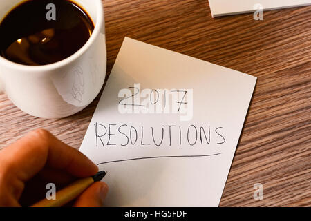 closeup of a young caucasian man with a pen in his hand writing the text 2017 resolutions in a piece of paper, on - Stock Photo