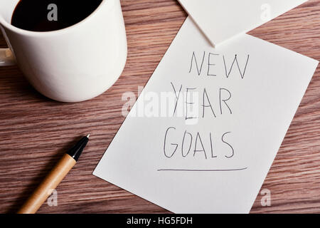 closeup of a cup of coffee, a pen and a piece of paper with the text new year goals handwritten in it, on a wooden - Stock Photo
