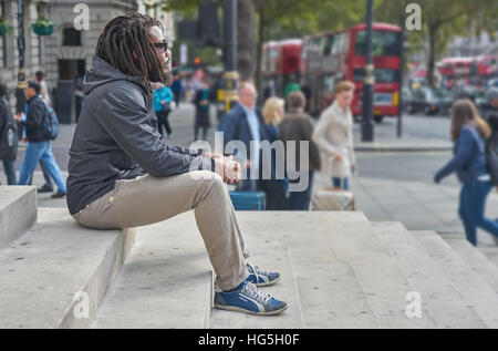 black man.  Man contemplating.   dreadlocks.  rastafarian.   Alone in the city. - Stock Photo