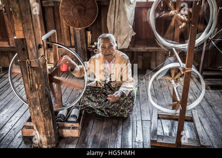 Woman worker weaves fabric in a weaving factory on Inle Lake. - Stock Photo