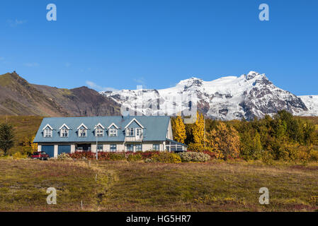 Landscape with an icelandic home and snowy mountains in the background. - Stock Photo