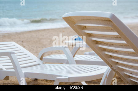 Reclining chairs on a beach in a sunny day in front of the beach. - Stock Photo