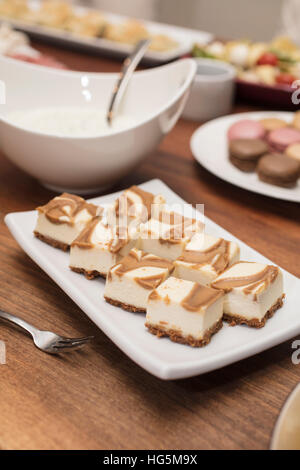 Vanilla Cheesecake squares swirled with caramel, with cold cuts and quiche appetizers in the background - Stock Photo