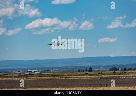 NAKAJIMA KI-43 OSCAR flying, front view with farm land, blue sky and white puffy clouds - Stock Photo