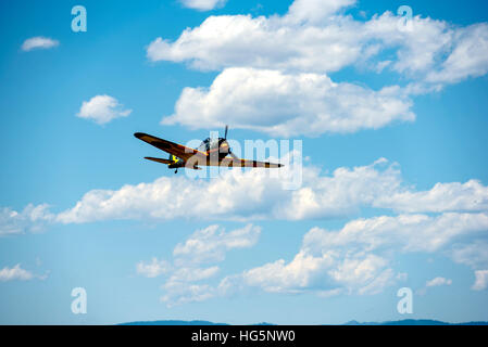 NAKAJIMA KI-43 OSCAR flying, front and bottom view, blue sky and white puffy clouds - Stock Photo