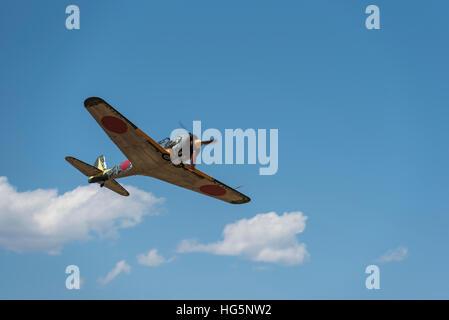 NAKAJIMA KI-43 OSCAR flying, underside view, blue sky and white puffy clouds - Stock Photo