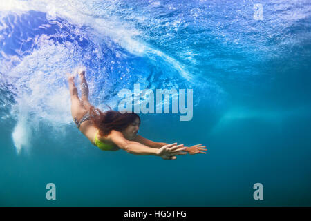 Young sportive girl in bikini in action. Fit woman swim underwater, dive under breaking ocean wave. Healthy lifestyle. - Stock Photo