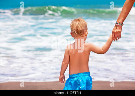 Happy family travel - mother, baby son walk with fun on black sand beach run to sea surf for swimming. Active parents - Stock Photo