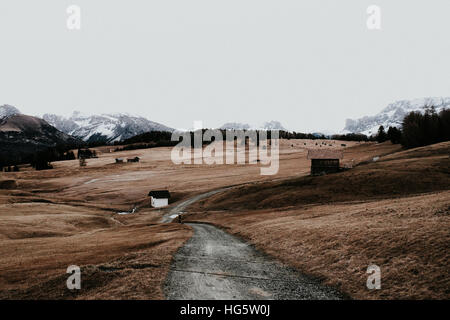 A path is leading through a field between mountain ranges with a few houses. - Stock Photo