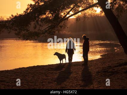 Couple walking their dog beside a lake. - Stock Photo