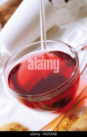 Glass of fruit tea resting on a bed of sugar with rock candy and brown sugar - Stock Photo