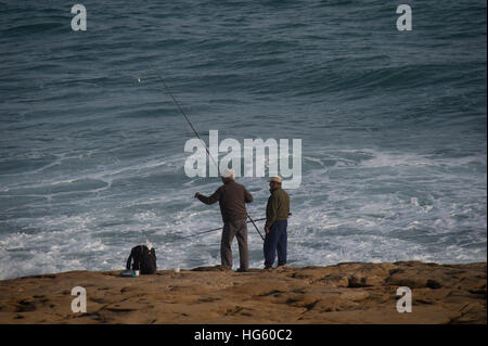 two men fishing off the rocks in Luz Portugal - Stock Photo