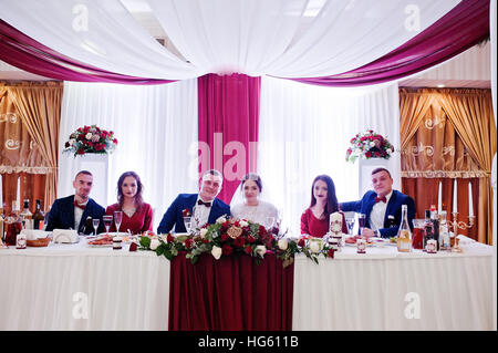 Wedding couple with best mans and bridesmaids sitting on table at restaurant. - Stock Photo