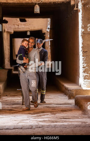 Ksar Elkhorbat, Morocco.  Two Men and Young Boy Walking in the Casbah. - Stock Photo