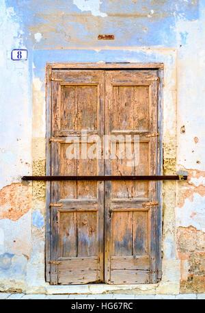 old wooden door locked with iron bar - Stock Photo