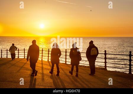 Coastal promenade walkway, sunset, people, shadow, walking, silhouette, sun, sky, person, water, lifestyle, light, - Stock Photo