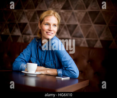 Pretty young blond woman  sitting in cafe - Stock Photo