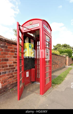 An old red British telephone box in Cossall Village, Nottingham, UK. Now converted into an emergency defibrillator - Stock Photo