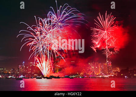 Bright red balls of new year eve fireworks in Sydney across illuminated waters of Harbour over skyscrapers of city - Stock Photo