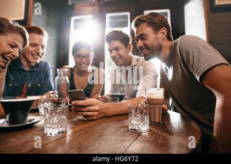 Group of friends sitting around a cafe table and looking at mobile phone. Young men and women looking at pictures - Stock Photo