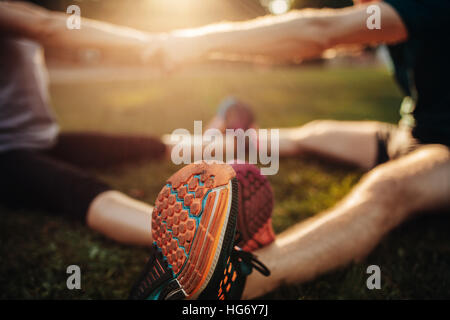 Feet of young man and woman exercising together in the park. Focus on shoes of couple working out together. - Stock Photo