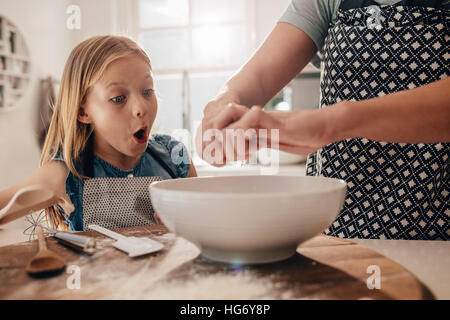 Excited young girl with mother preparing dough for baking. Woman hands cooking with daughter standing by in kitchen. - Stock Photo