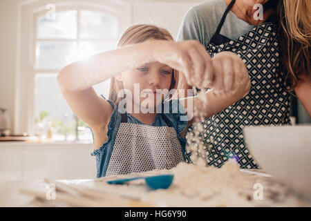 Beautiful little girl learns to cook a meal in the kitchen. Girl making a dough for baking with her mother standing - Stock Photo