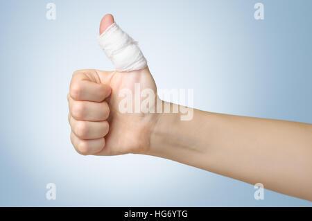 Injured painful finger with white bandage - Stock Photo