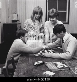 1960s, historical, two boys sitting at a table, with two girls looking on, playing 'English draughts', a strategy - Stock Photo