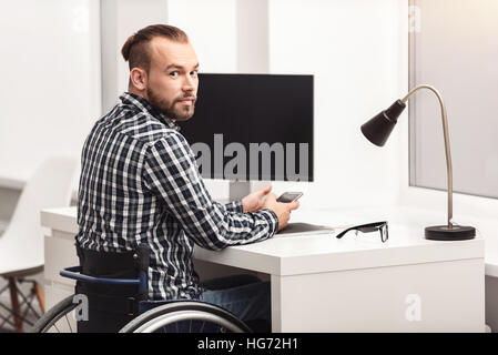 Young physically challenged person working in home office - Stock Photo