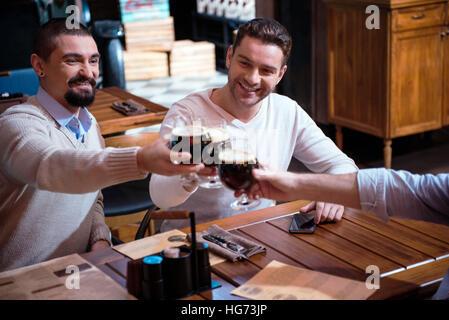 Positive joyful friends cheering with beer - Stock Photo
