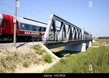 Bar-bistro unit of passenger train passing over small bridge - Stock Photo