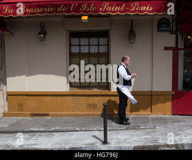 French waiter is lighting a cigarette in front of La Brasserie De L'Isle Saint Louis restaurant in Paris, France - Stock Photo