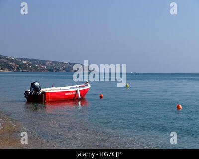 Red motorboat anchored off Skala beach on the Island of Kefalonia in Greece. - Stock Photo